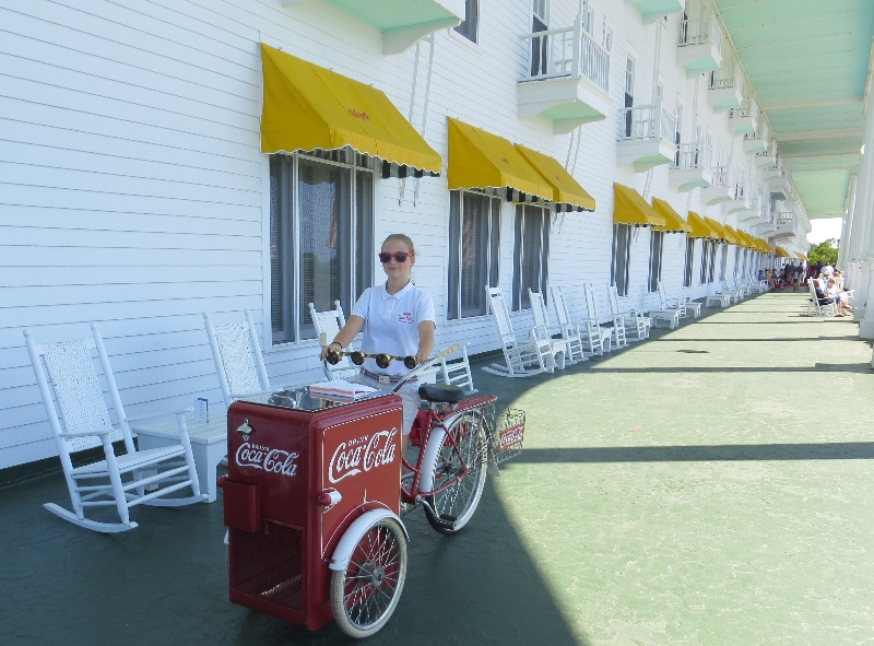Hostess pedals antique coca-cola cooler along massive front porch at the Grand Hotel