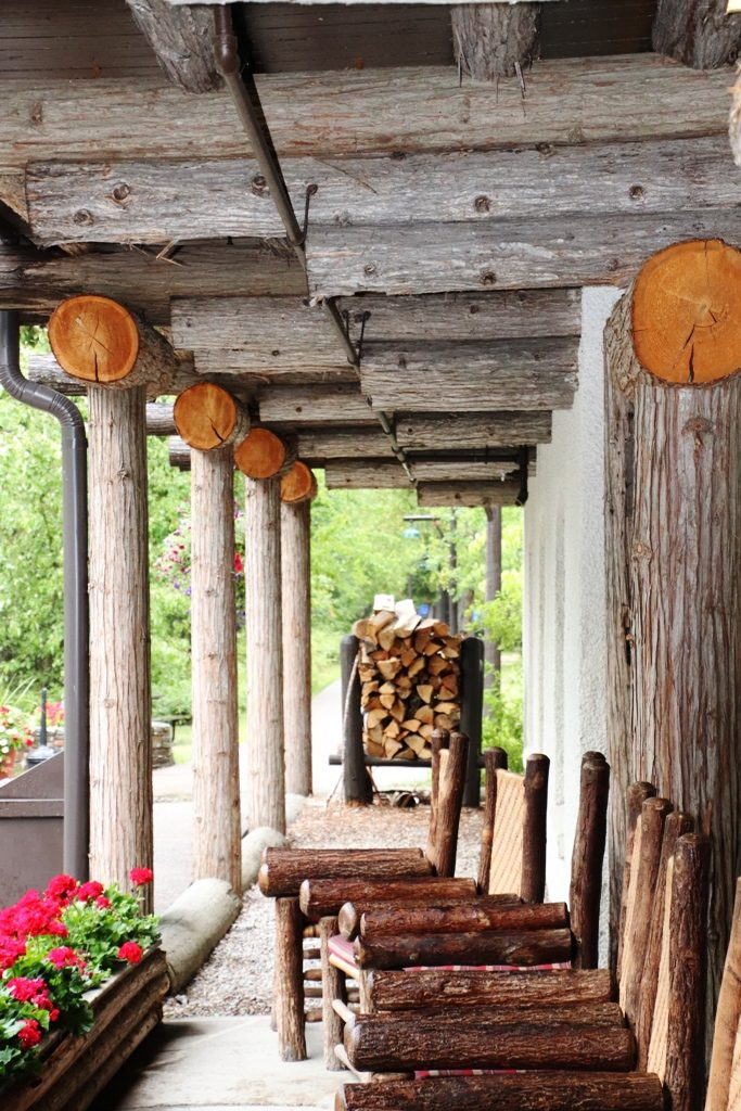 Lake McDonald Lodge porch shows exposed log beams and log chairs for sitting